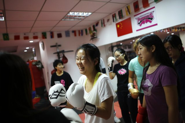 A woman laughs during a boxing class at Princess Women's Boxing Club in Shanghai December 8, 2014. (Photo by Carlos Barria/Reuters)