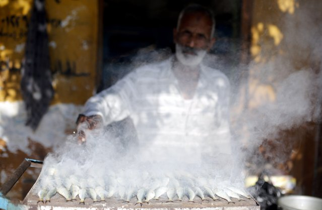 A man grills fish to sell, in front of his house in the fishermen's village in El Max in the Mediterranean city of Alexandria October 18, 2014. (Photo by Amr Abdallah Dalsh/Reuters)