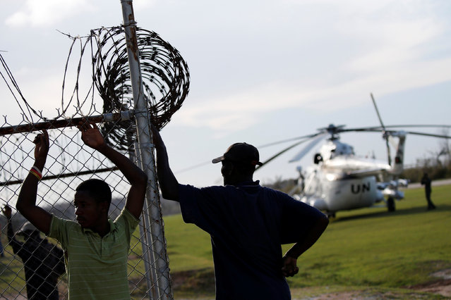 Men stand by a fence next to a United Nations helicopter at the airport after Hurricane Matthew passes Jeremie, Haiti, October 7, 2016. (Photo by Carlos Garcia Rawlins/Reuters)