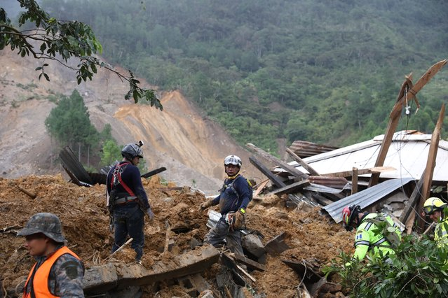 Members of search and recovery teams search for survivors in the debris of a massive, rain-fueled landslide in the village of Queja, in Guatemala, Saturday, November 7, 2020, in the aftermath of Tropical Storm Eta. (Photo by Esteban Biba/Pool Photo via AP Photo)