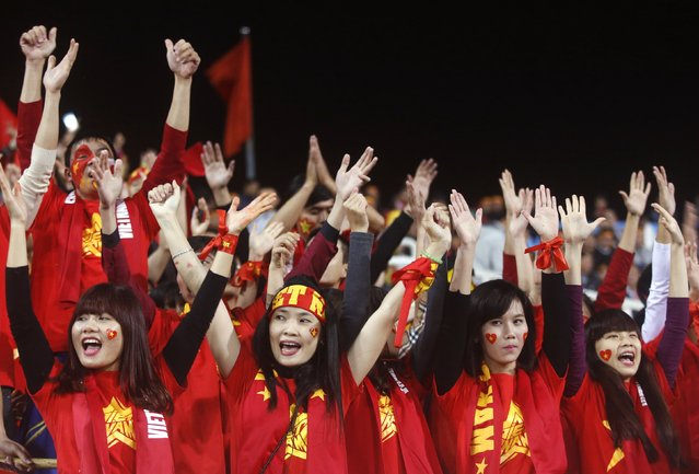 Vietnamese fans, dressed in the colours of their national flag, cheer before the second leg of their ASEAN Football Federation Suzuki Cup 2014 semi-final match against Malaysia at My Dinh stadium in Hanoi December 11, 2014. (Photo by Reuters/Kham)