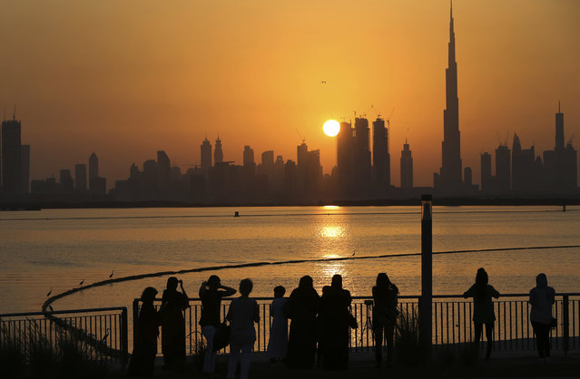 """In this October 7, 2016 file photo, people watch the sunset over the skyline, with Burj Khalifa at right, in Dubai, United Arab Emirates. The United Arab Emirates announced on Saturday a major overhaul of the country's Islamic personal laws, allowing unmarried couples to cohabitate, loosening alcohol restrictions and criminalizing so-called """"honor killings"""". (Photo by Kamran Jebreili/AP Photo/File)"""