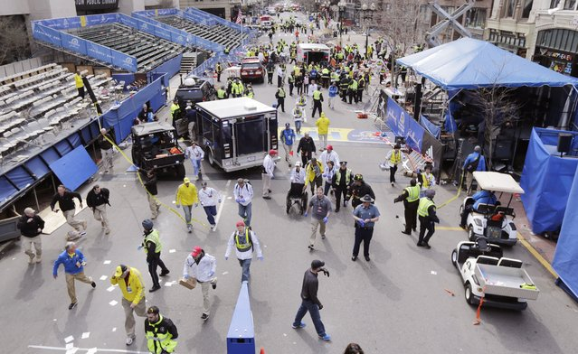 Police clear the area at the finish line of the 2013 Boston Marathon following an explosion in Boston, Monday, April 15, 2013. (Photo by Charles Krupa/AP Photo)