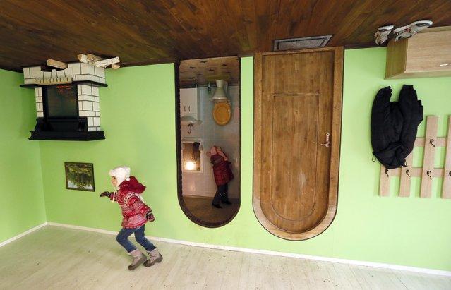 Children visit a house built upside-down in Russia's Siberian city of Krasnoyarsk, December 14, 2014. (Photo by Ilya Naymushin/Reuters)