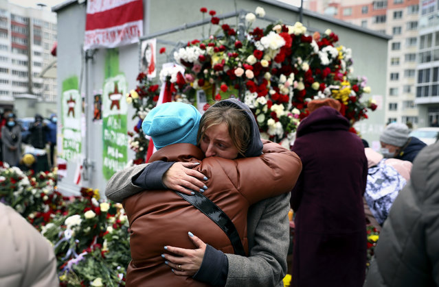 Two women embrace each other as people gather to honor 31-year-old Raman Bandarenka, who died Thursday at a Minsk hospital after several hours of surgery due to serious injuries, in Minsk, Belarus, Friday, November 13, 2020. Thousands of people have rallied in Belarus on Friday following the death of a 31-year-old opposition supporter who died in a hospital after he was reportedly beaten by security forces, and the European Union condemned the continued violent crackdown that Belarusian authorities have waged on peaceful protesters. (Photo by AP Photo/Stringer)
