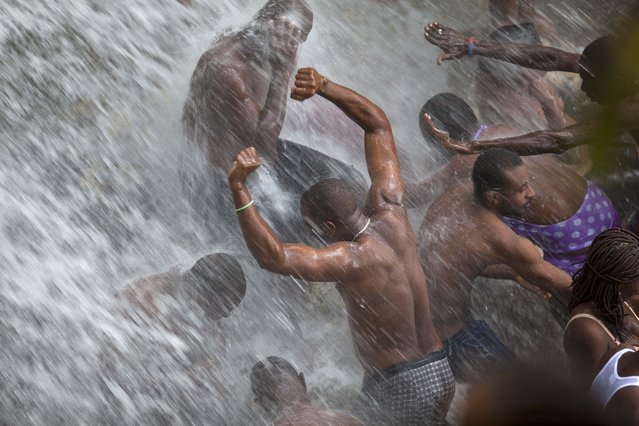 In this July 16, 2014 file photo, voodoo pilgrims bathe in a waterfall believed to have purifying powers during the annual celebration in Saut d' Eau, Haiti. The annual pilgrimage is made in honor of Haiti's most celebrated patron saint, Our Lady of Mount Carmel, who is supposed to have appeared on a palm tree in 1847 in the Palm Grove in Saut d'Eau and was integrated into Haiti's voodoo culture as the goddess of love. (Photo by Dieu Nalio Chery/AP Photo)