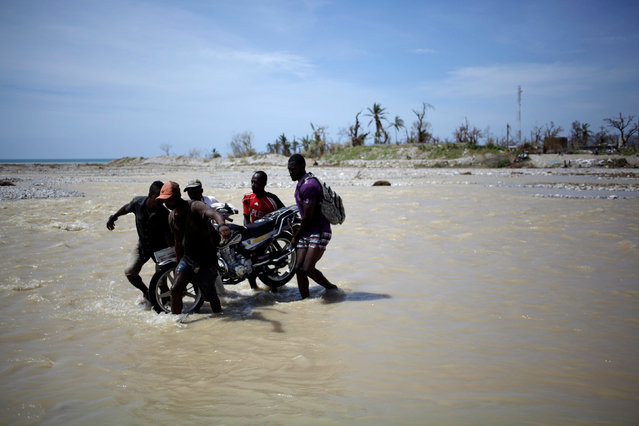 Men carry a motorbike as they cross a river after Hurricane Matthew in Les Anglais, Haiti, October 10, 2016. (Photo by Andres Martinez Casares/Reuters)