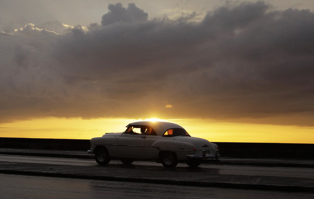 "A U.S.-made private collective taxi drives down Havana's seafront boulevard ""El Malecon"" during sunset July 13, 2013. (Photo by Desmond Boylan/Reuters)"