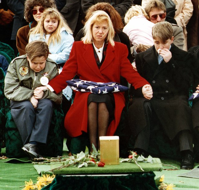 "Mrs. Gayle Edwards, of Grand Rapids, Mich., holds the hands of her sons Bennett, 11, left, and Spencer, 13, during the funeral for her husband, Marine Capt. Jonathon ""Jack"" Edwards, at Arlington National Cemetery, in Arlington, Va., on February 15, 1991. Seated at left rear is her daughter Adrianna, 8. Edwards was killed while flying a support mission in Saudi Arabia during the Gulf War. (Photo by Doug Mills/AP Photo)"