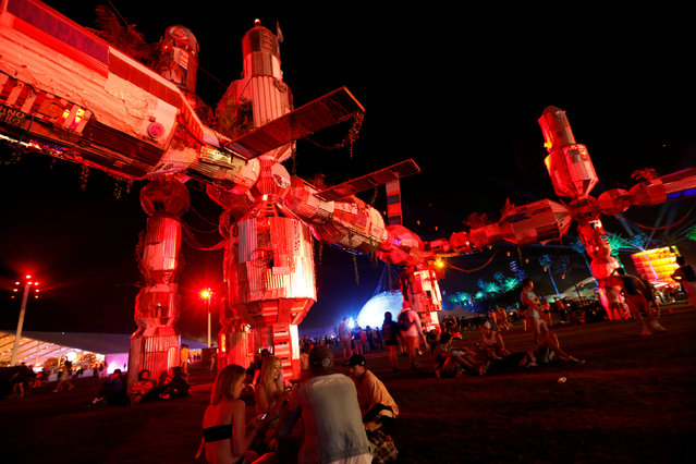 """Concertgoers sit by an installation called """"Palm-3 World Station"""" at the Coachella Valley Music and Arts Festival in Indio, California, U.S., April 13, 2018. (Photo by Mario Anzuoni/Reuters)"""
