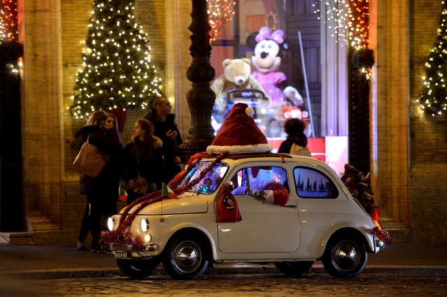 A man dressed as Santa Claus drives his old Fiat 500 in the Piazza Venezia in central on December 23, 2014, as people prepare for Christmas. (Photo by Filippo Monteforte/AFP Photo)