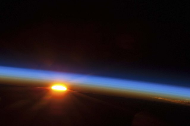 In this image provided by NASA, the sun rises over the South Pacific Ocean photographed by one of the Expedition 35 crew members aboard the Earth-orbiting International Space Station between 4 and 5 a.m. local time, May 5, 2013. (Photo by NASA)