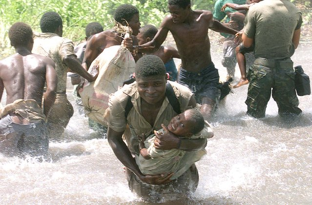 A Mozambican soldier runs with a child through flood water towards a helicopter in the central district of Cocorico March 2, 2001. (Photo by Juda Ngwenya/Reuters)