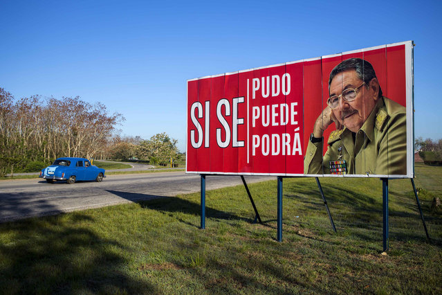 """A car drives by a billboard that reads in Spanish """"Ít was, is and will be done"""", with a picture of Cuba's President Raul Castro on the outskirts of Havana, Cuba, Wednesday, April 18, 2018. Cuba's legislature opened the two-day session that is to elect a successor to President Castro. (Photo by Desmond Boylan/AP Photo)"""