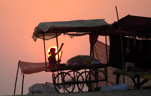 An Indian child sits on a handcart as she makes flower garlands to sell it to devotees preparing to perform rituals at Sangam in Allahabad on October 18, 2016. (Photo by Sanjay Kanojia/AFP Photo)