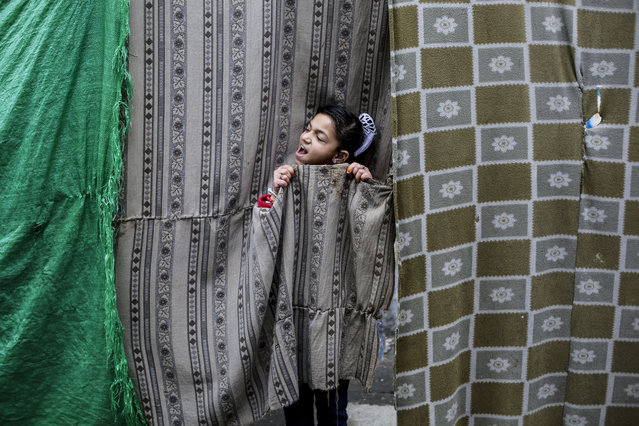 A Palestinian girl seen in a tent during a rainy day in Jabalia camp in the northern Gaza Strip on December 16, 2020. (Photo by Mahmoud Issa/SOPA Images/Rex Features/Shutterstock)