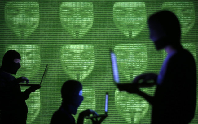 Bosnia and Herzegovina: People are silhouetted as they pose with laptops in front of a screen projected with Guy Fawkes aka Anonymus masks and binary code, in this picture illustration taken in Zenica October 29, 2014. (Photo by Dado Ruvic/Reuters)