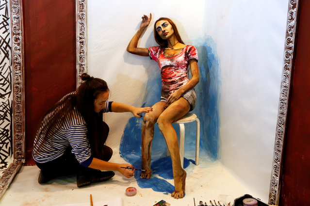 "Russian artist Maria Gasanova (L) works with model Inna Magomedova on her ""The Alive Painting"" body art work during the Art Krasnoyarsk annual festival in Siberian city of Krasnoyarsk, Russia, October 26, 2016. (Photo by Ilya Naymushin/Reuters)"