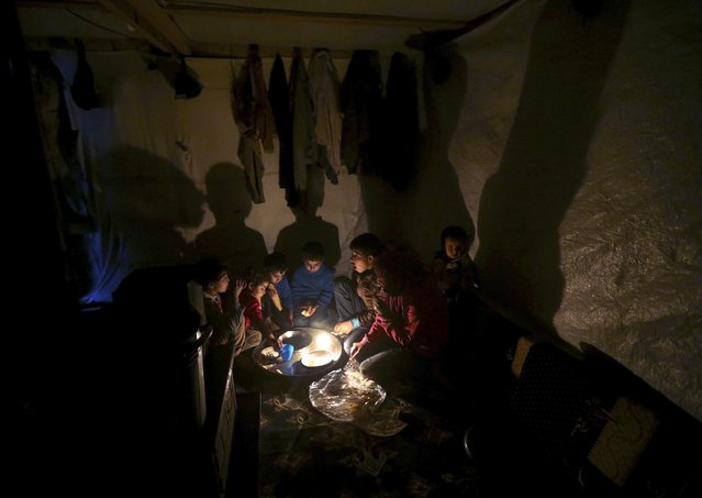Syrian refugee children sit on the ground inside their tent home as they take their dinner at a Syrian refugee camp, in Deir Zannoun village in the Bekaa valley, eastern Lebanon, on Monday, January 5, 2015. (Photo by Hussein Malla/AP Photo)