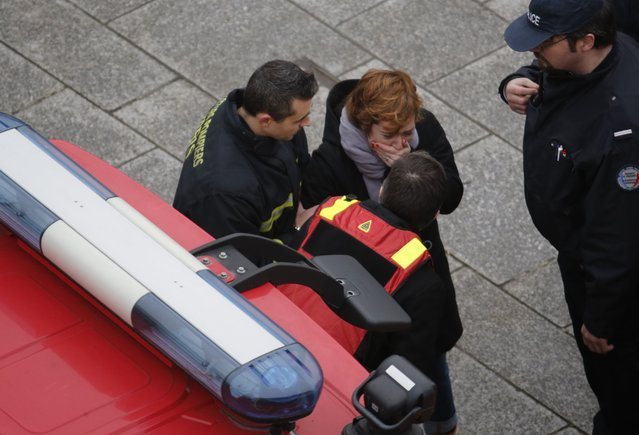 A distressed woman is assisted  by firemen near the scene after a shooting at the Paris offices of Charlie Hebdo, a satirical newspaper, January 7, 2015. (Photo by Christian Hartmann/Reuters)