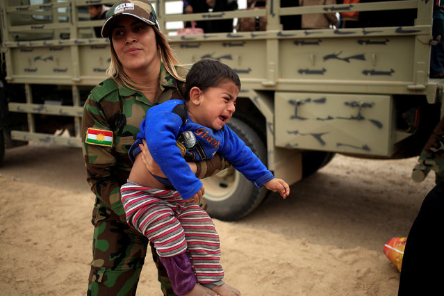 A Kurdish female Peshmerga soldier carries a newly internally displaced boy as he cries upon his arrival at Al Khazar camp near Hassan Sham, east of Mosul, Iraq October 28, 2016. (Photo by Zohra Bensemra/Reuters)