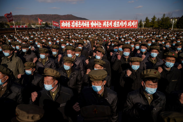 In a photo taken on November 20, 2020, divisions of returning elite party members attend a meeting to pledge loyalty before the portraits of late North Korean leaders Kim Il Sung and Kim Jong Il, upon their arrival at Kumsusan palace in Pyongyang, following their deployment to rural provinces to aid in recovery efforts amid damage caused by a September typhoon. (Photo by Kim Won Jin/AFP Photo)