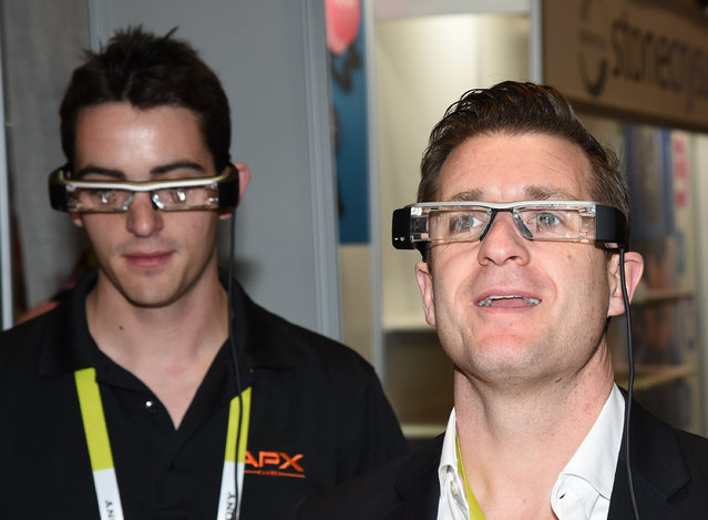 Paul Setlak (L) and Brett Leary try out Epson's BT-200 Moverio smart glasses at the 2015 International CES at the Sands Expo and Convention Center on January 6, 2015 in Las Vegas, Nevada. The USD 699 augmented reality glasses have a front-facing camera for video capture and virtual reality gaming. (Photo by Ethan Miller/Getty Images)