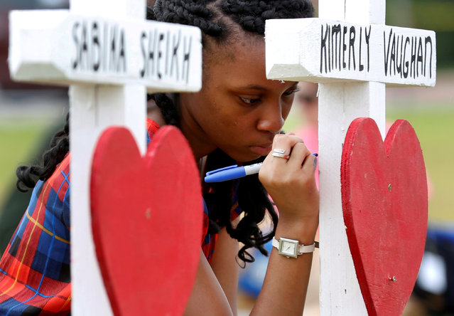 Jai Gillard, a freshman at Santa Fe High School, writes a message on a cross at a makeshift memorial left in memory of the victims killed in a shooting in Santa Fe, Texas, U.S., May 21, 2018. (Photo by Jonathan Bachman/Reuters)