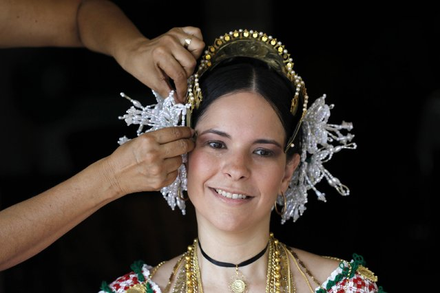 "A woman is helped with adorning her hair with jewelry, part of the traditional clothing known as ""Pollera"", before the annual Thousand Polleras parade in Las Tablas, in the province of Los Santos January 10, 2015. According to local residents, the Pollera dates back to the 18th century and was worn by the Spanish lower classes. (Photo by Carlos Jasso/Reuters)"