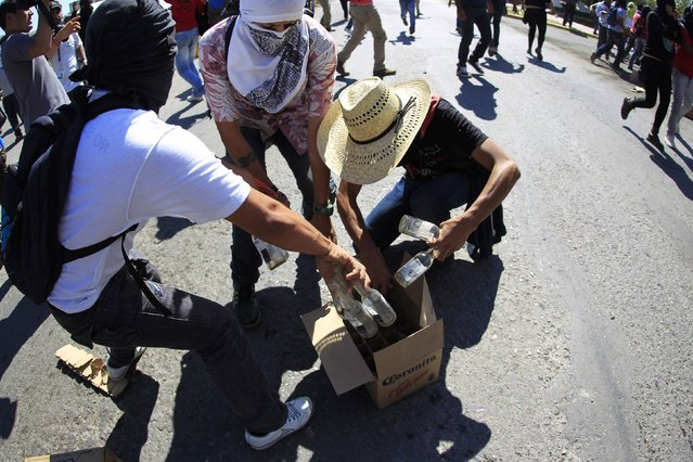 Activists taken bottles of a beer to throw against the military police during a demonstration in the military zone of the 27th infantry battalion, in Iguala, Guerrero January 12, 2015. (Photo by Jorge Dan Lopez/Reuters)