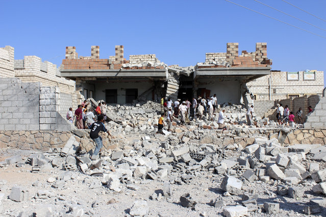 People gather outside a house destroyed by an air strike on a suspected hideout of al Qaeda militants in al-Shiher city of Yemen's southeastern province of Hadramount November 22, 2013. (Photo by Reuters/Stringer)