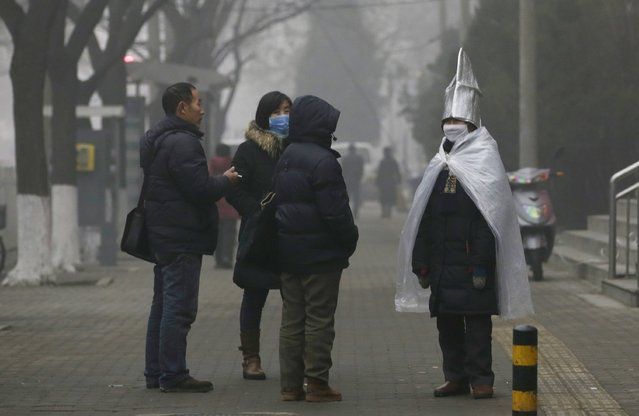A protester wearing a mask stands near the headquarters of Supreme People's Court of China as smog covers China's capital Beijing on an extremely polluted day, December 1, 2015. (Photo by Jason Lee/Reuters)