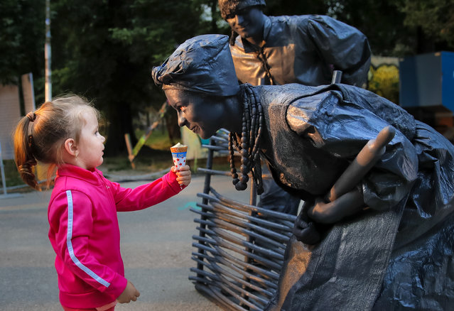 """In this Thursday, May 24, 2018, photograph, a child offers ice-cream to artists of Ukraine's Artel Myth theatre performing """"A day in the life of Ukrainians"""" at the Living Statues International Festival, in Bucharest, Romania. (Photo by Vadim Ghirda/AP Photo)"""