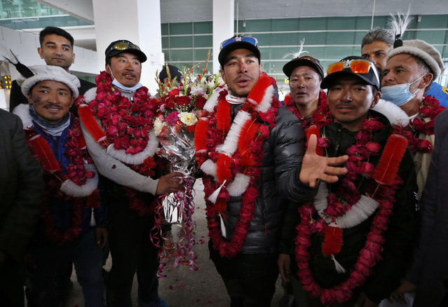 Nepalese climber Nirmal Purja, center, and his team, who recently made history by scaling the K2 summit in the winter season, are greeted by local tour operators upon their arrival at airport in Islamabad, Pakistan, Thursday, January 21, 2021. Winter winds on K2 can blow at more than 200 km per hour (125 miles per hour) and temperatures can drop to minus 60 C (minus 76 F), an official of Pakistan's Alpine Club, Karrar Haideri said. (Photo by Anjum Naveed/AP Photo)