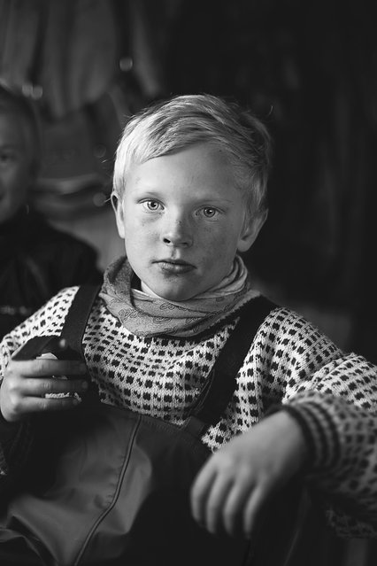 """Merit Winner: """"Children of Reindeer"""". Mikael Ánde, a child of Sámi reindeer herders, takes a break indoors after a long, cold day of rounding up the animals for vaccinations and slaughter. Children of reindeer herders learn to handle these animals and the land they thrive in from infancy – young Mikael here knew far more about the ways of nature than I could ever hope to learn. Location: Magerøya, Norway. (Photo and caption by Michelle Schantz/National Geographic Traveler Photo Contest)"""