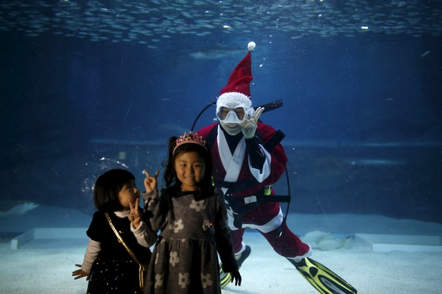 "A diver dressed in a Santa Claus costume poses for photographs behind girls as he swims with sardines during a promotional event for the Christmas ""Sardines Feeding Show with Santa Claus"" at the Coex Aquarium in Seoul, South Korea, December 9, 2015. (Photo by Kim Hong-Ji/Reuters)"
