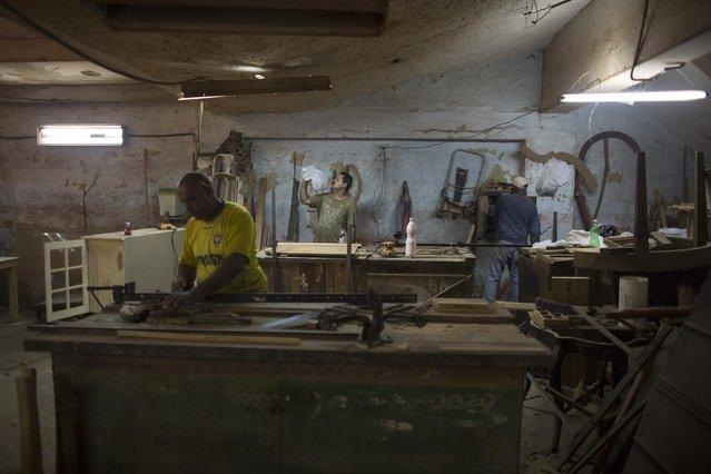 Wood worker Manuel Afonso (C), 51, drinks water inside a carpentry in downtown Havana January 15, 2015. (Photo by Alexandre Meneghini/Reuters)