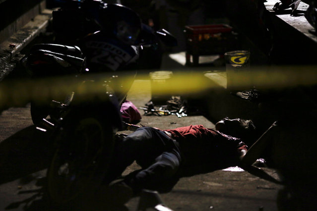 The body of a man who was killed by two motorcycle-riding gunmen is seen behind a police line during investigation in Manila, Philippines early October 29, 2016. (Photo by Damir Sagolj/Reuters)