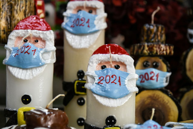 Christmas candles depicting Santa Claus wearing a protective mask are displayed at the shop of candlemaker Alexis Gerakis, as the COVID-19 pandemic continues, in Thessaloniki, Greece, November 16, 2020. (Photo by Alexandros Avramidis/Reuters)