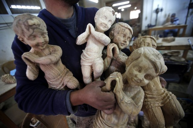 A Palestinian carpenter carries wooden sculptures of Christian religious figures through a workshop in the West Bank city of Bethlehem, 17 December 2015. The figures are being crafted ahead of the celebration by most Christians of the birth of Christ, celebrated 24 or 25 December, or 07 January amongst the Orthodox community. (Photo by Abed Al Hashlamoun/EPA)