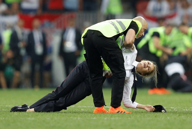 Stewards remove pitch invaders, p*ssy Riot members during the 2018 FIFA World Cup Final between France and Croatia at Luzhniki Stadium on July 15, 2018 in Moscow, Russia. The pitch invasion sparked a furious debate online with many tweeting support for the group, while others claimed they had spoiled a key moment for Croatia. (Photo by Darren Staples/Reuters)