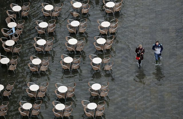 People walk on the flooded St. Mark's Square during a period of seasonal high water and on the first day of carnival, in Venice February 1, 2015. (Photo by Stefano Rellandini/Reuters)