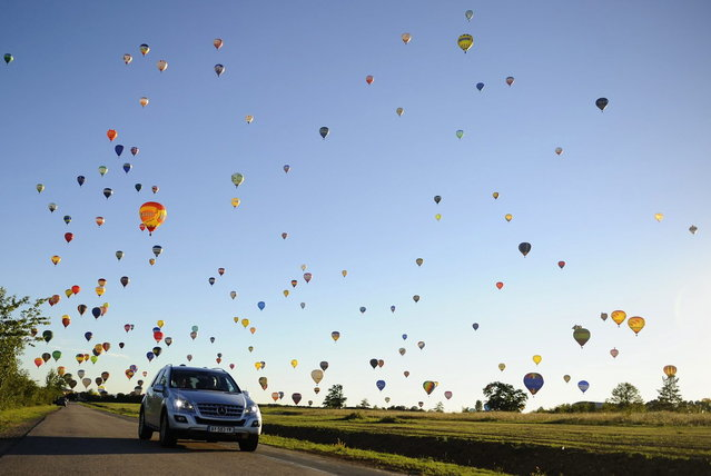 "A car drives on a road while hot-air balloons fly over Chambley-Bussieres, eastern France, on July 31, 2013, to try to set a world record with 408 balloons in the sky, as part of the yearly event ""Lorraine Mondial Air Ballons"", an international air-balloon meeting. (Photo by Jean-Christophe Verhaegen/AFP Photo)"
