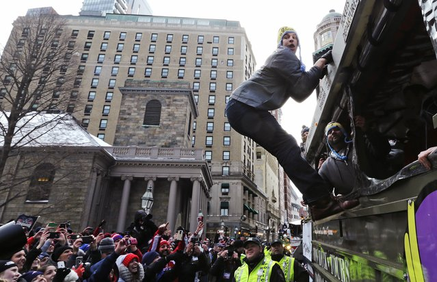 New England Patriots tight end Rob Gronkowski hangs out of a duck boat as fans cheer during a parade in Boston, Wednesday, February 4, 2015, to honor the NFL football team's victory over the Seattle Seahawks in Super Bowl XLIX in Glendale, Ariz. (Photo by Charles Krupa/AP Photo)