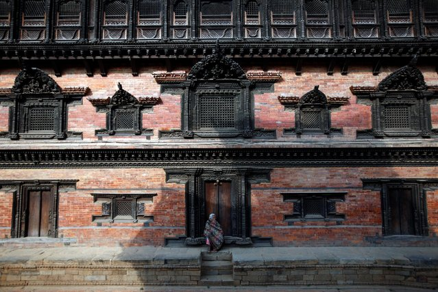 A woman sits at the courtyard of Durbar Square in Bhaktapur, Nepal November 23, 2016. (Photo by Navesh Chitrakar/Reuters)
