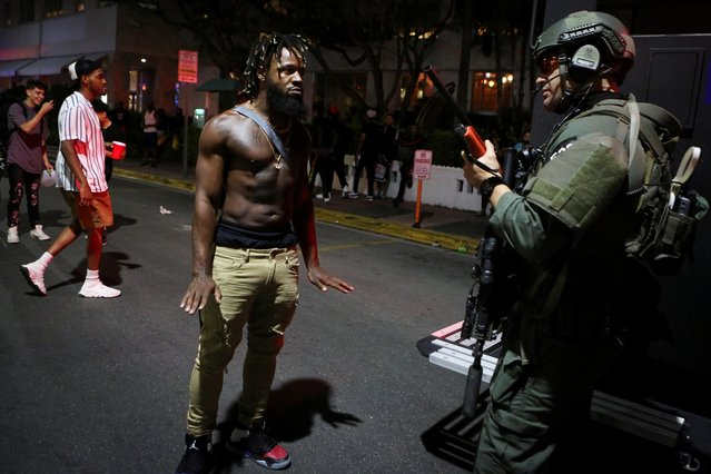 A man talks to a police officer as revelers enjoy spring break festivities despite an 8pm curfew imposed by local authorities, amid the coronavirus disease (COVID-19) pandemic, in Miami Beach, Florida, U.S., March 20, 2021. (Photo by Marco Bello/Reuters)