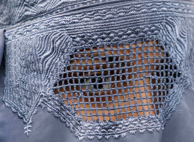 An Afghan refugee woman, clad in a burqa, waits with others to be repatriated to Afghanistan, at the United Nations High Commissioner for Refugees (UNHCR) office on the outskirts of Peshawar, February 2, 2015. (Photo by Fayaz Aziz/Reuters)