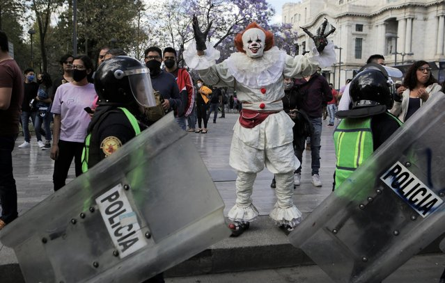 Police officers walk while holding shields as a person dressed as a clown gestures, during a protest in support of Victoria Salazar, a Salvadoran woman who died after a Mexican female police officer was seen in a video kneeling on her back, in Mexico City, Mexico on April 2, 2021. (Photo by Raquel Cunha/Reuters)