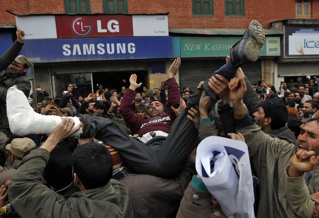 Government employees lift their colleague as they shout slogans during a protest in Srinagar February 7, 2015. Indian police detained dozens of demonstrators on Saturday during the protest demanding greater regularization of temporary jobs and a hike in salaries, protesters said. (Photo by Danish Ismail/Reuters)