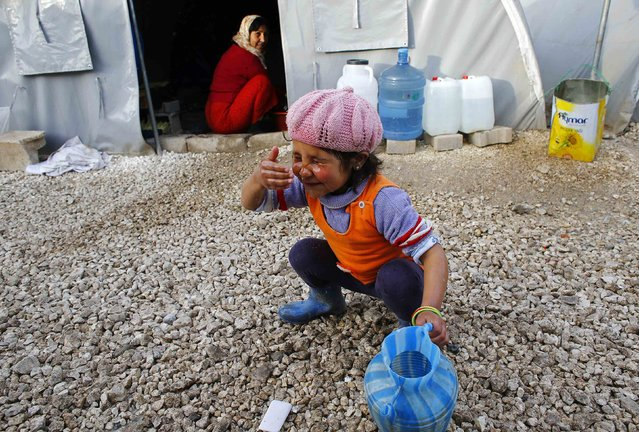A Kurdish refugee girl from the Syrian town of Kobani washes her face at a refugee camp in the border town of Suruc, Sanliurfa province February 2, 2015. (Photo by Umit Bektas/Reuters)
